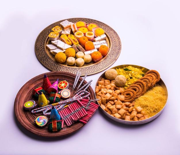 ディワリのコンセプトを示す別のプレートにさまざまな爆竹を添えたインドの甘い食べ物