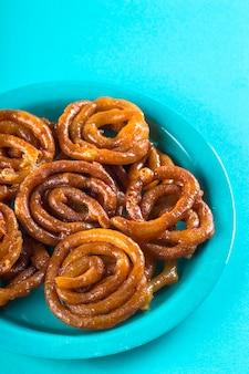 Indian sweet jalebi, indian dessert jalebi or imarti or imarati or jilbi on blue