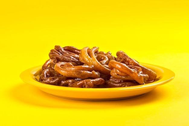 Indian sweet jalebi, indian dessert jalebi or imarti or imarati or jilbi on yellow