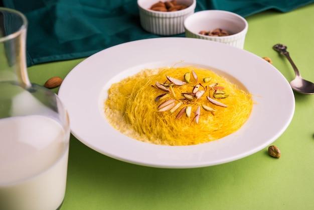 Индийский сладкий кесар сутарфени или сутар фени, или фирни, или севийан, или лакча, измельченный, слоеный рисовая мука, обжаренная в топленом масле, смешанная с топленым сахаром для образования сахарной ваты, с фисташками и миндалем