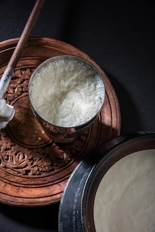 Indian sweet lassi made up of milk, curd, sugar and salt mixed with ice cubes, served in a jumbo steel glass, prepared in traditional earthen pot