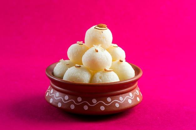 インドの甘いまたはデザート-ラスガラ、ピンクの背景の粘土ボウルで有名なベンガル語の甘い。