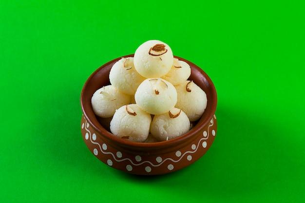 インドの甘いまたはデザート-ラスグラ、緑の背景に粘土ボウルで有名なベンガル語の甘い