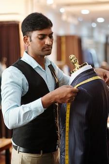 그가 클라이언트를 위해 만들고있는 수트 재킷의 어깨 사이 거리를 측정하는 인도 재단사