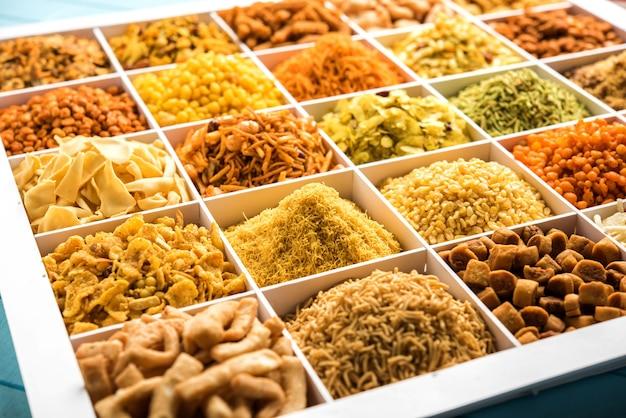 Sev, chivda, farsan, mix, boondi, bakarwadi 등과 같은 인도 티 타임 스낵은 세포가 있는 흰색 나무 상자에 제공됩니다. 선택적 초점