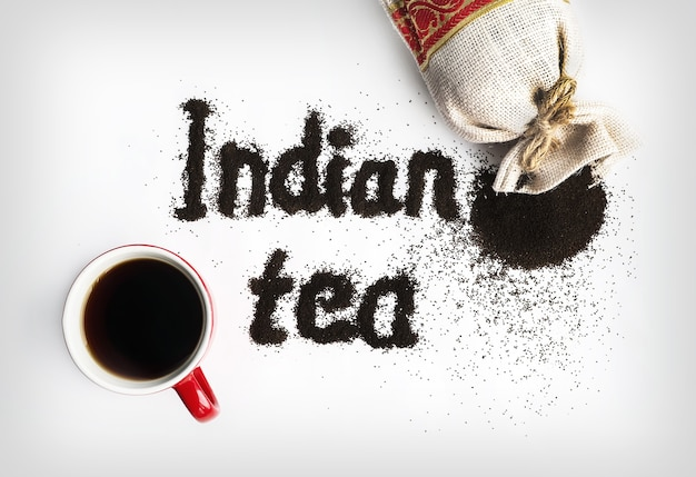 Indian tea - the words written on the white table. the inscription is black tea top view.