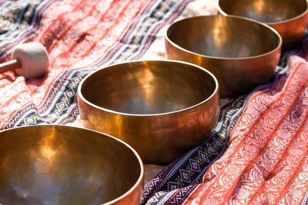 Индийские тибетские бронзовые лечебные чаши лежат на сари в перспективе. поющие лечебные чаши тибетской народной медицины. звучит священная музыка для исцеления.