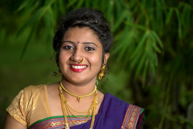 Индийская традиционная красивая молодая женщина в сари позирует на открытом воздухе
