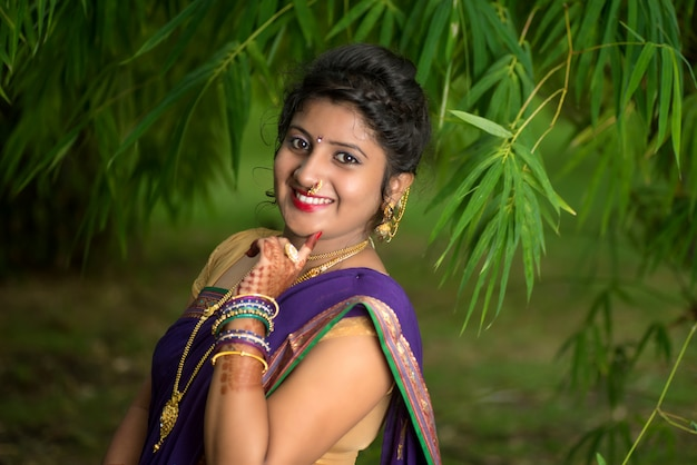 Indian traditional beautiful young woman in saree posing outdoors
