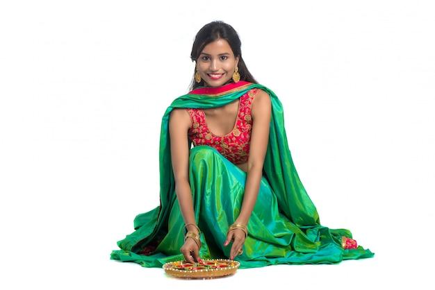Indian traditional girl holding diya and celebrating diwali or deepavali