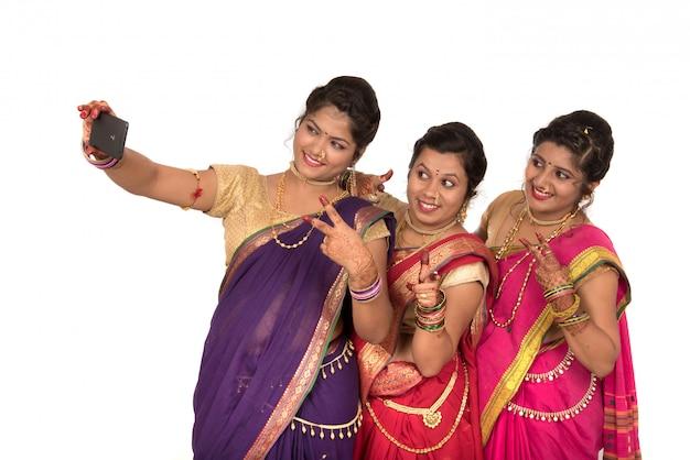 Индийские традиционные девушки, принимающие селфи с смартфон на белой поверхности