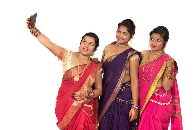 白のスマートフォンでselfieを取るインドの伝統的な女の子