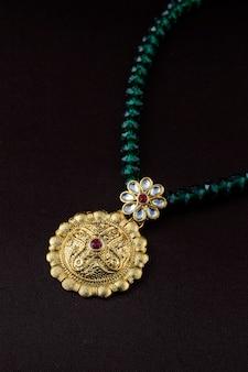 Индийские традиционные украшения, крупным планом кулон на темном фоне