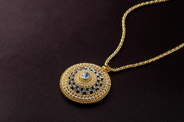 Indian traditional jewellery, close up of pendent on dark background