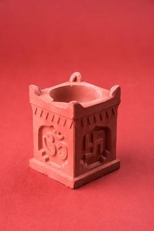 インドの伝統的な鍋またはtulsivrindavanまたはvrundavanとして知られる特別な石積み構造で、卍とオウムの執筆、聖なるヒンドゥー教のオブジェクト、孤立した選択的な焦点