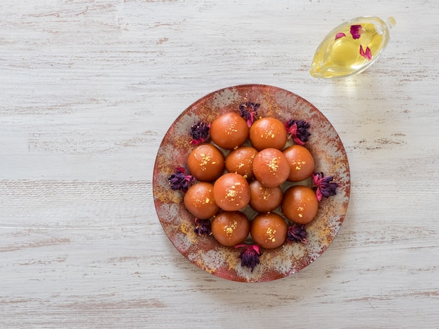 Indian traditional sweet gulab jamun on wooden table