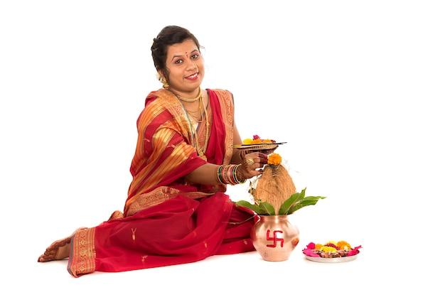 銅カラッシュで崇拝を行うインドの伝統的な女性