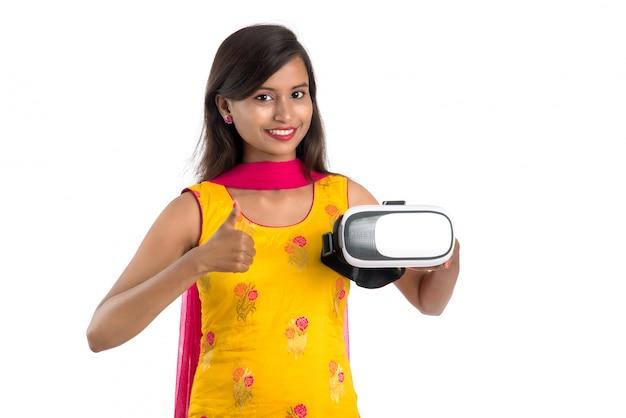 Индийская традиционная молодая женщина держа и показывая прибор vr, коробку vr, изумлённые взгляды, шлемофон стекел виртуальной реальности 3d, женщину с современной технологией воображения будущей на белизне.