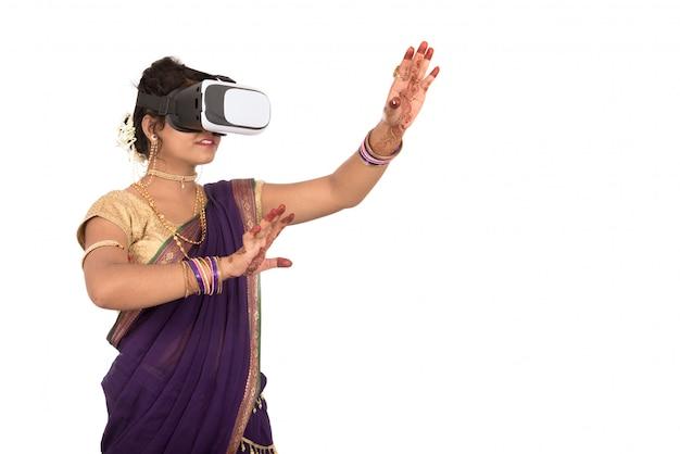 Индийская традиционная молодая женщина в сари, глядя хотя устройство vr