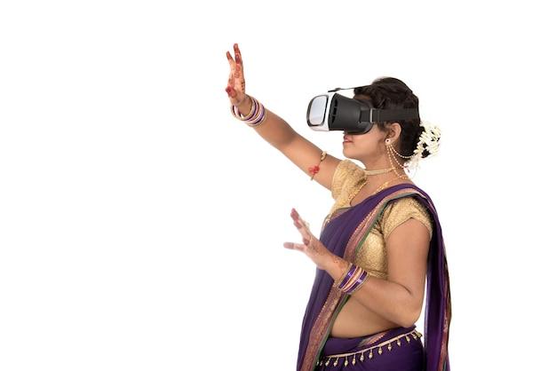 Индийская традиционная молодая женщина в сари, глядя на устройство vr