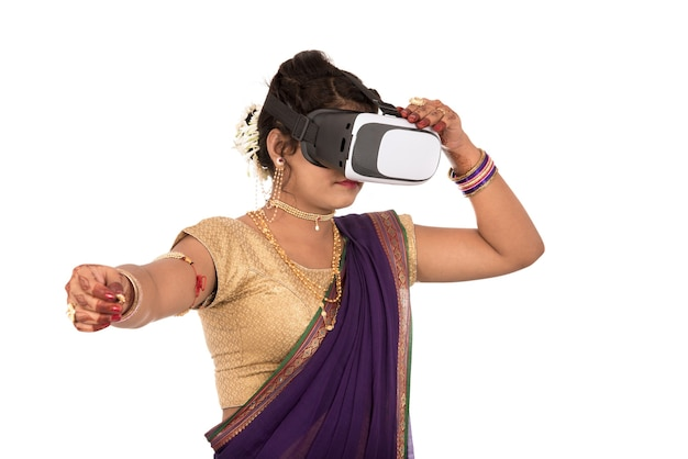 Indian traditional young woman in saree looking though vr device