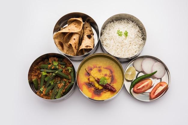 インドのベジタリアンランチボックスまたはオフィスまたは職場用のステンレス鋼で作られたティフィンには、ダルフライ、ビンディマサラ、チャパティとサラダのライスが含まれます
