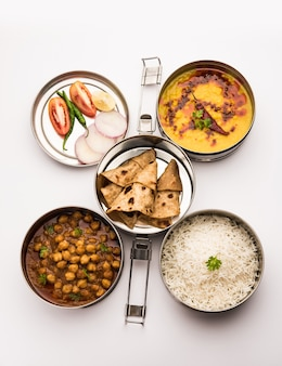 Indian vegetarian lunch box or tiffin made up of stainless steel for office or workplace, includes dal fry, chole masala, rice with chapati and salad