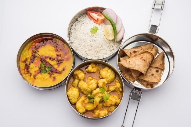 Indian vegetarian lunch box or tiffin made up of stainless steel for office or workplace, includes dal fry, gobi masala, rice with chapati and salad