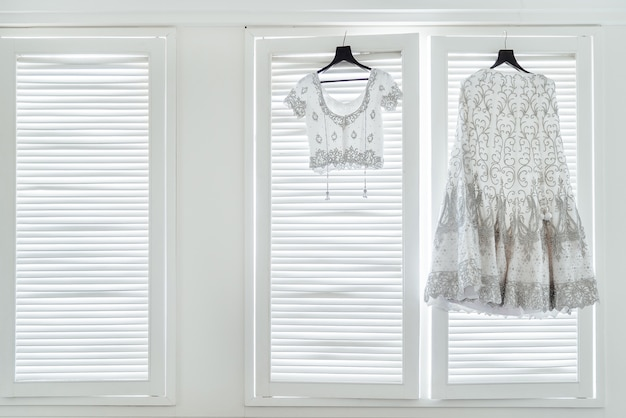 The indian wedding dress, saree and blouse hanging on the white windows