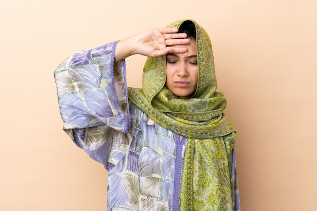 Indian woman on beige wall with tired and sick expression
