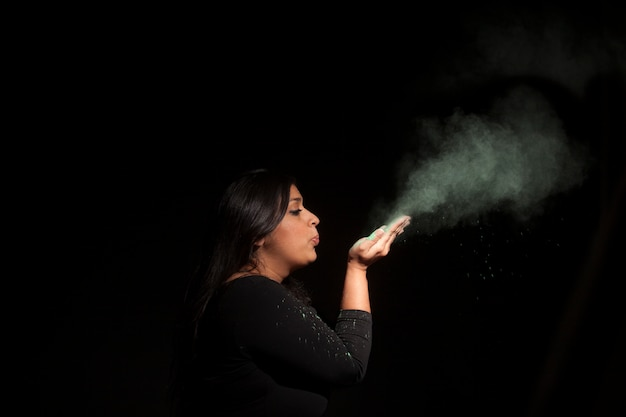 Indian woman blowing green dust isolated