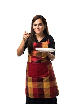앞치마를 입고 흰색 배경 위에 고립 된 다른 얼굴 표정으로 빈 세라믹 디너 접시와 그릇을 들고 인도 여자 요리사