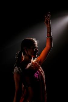 光と踊るインドの女性