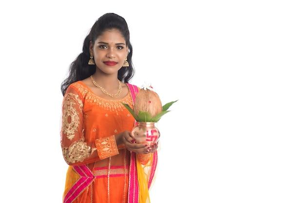 Индийская женщина держит традиционный медный калаш с кокосовым орехом и листом манго с цветочным декором, что важно на индийском индуистском фестивале и поклонении