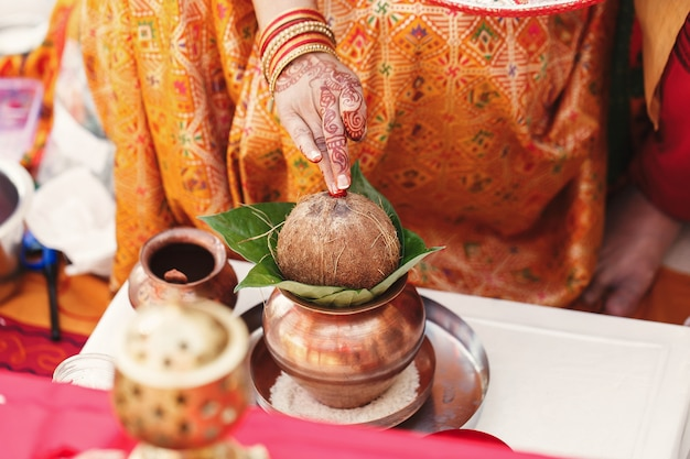 Indian woman holds a coconut over the mango leaves put in bronze