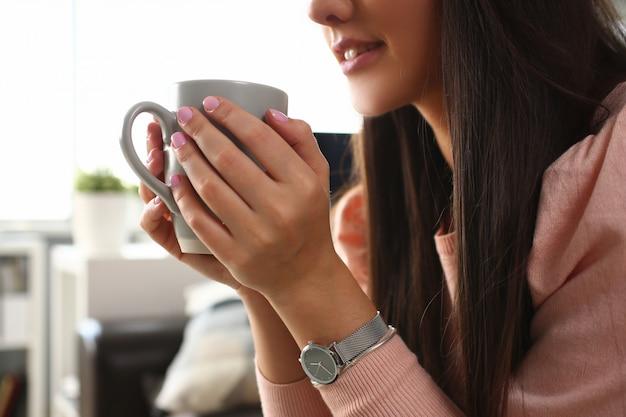 Indian woman holds mug her hand smiles