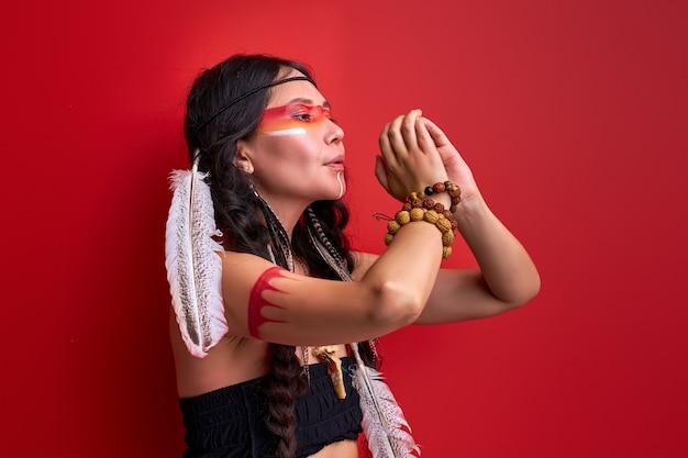 깃털을 가진 전통 민족 의상에서 인도 여자 사냥꾼