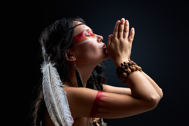 Indian woman immerse herself in hypnosis, shamaning alone isolated in studio, side view