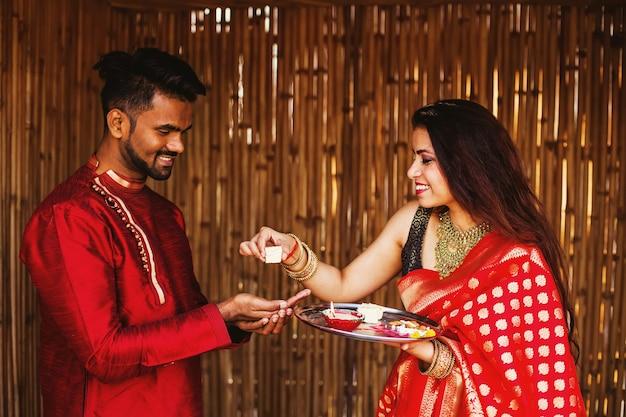 빨간 사리를 입은 인도 여성이 행복한 남자에게 프라사드를 제공합니다.