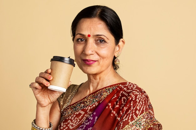 Индийская женщина в сари пьет кофе из макета бумажного стаканчика