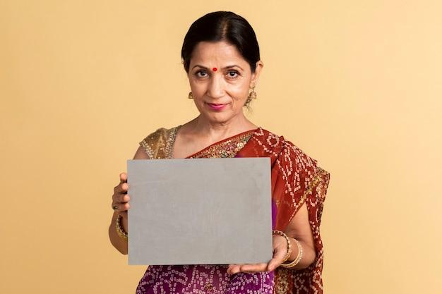 紙のモックアップを保持している伝統的なサリーのインドの女性