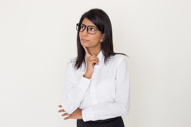 Индийская женщина в формальной одежде и очках, опираясь подбородок на указательный палец.
