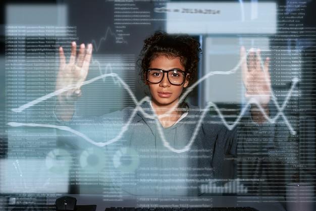 Индийская женщина смотрит графику на цифровых экранах