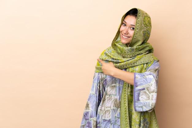 다시 가리키는 베이지 색 배경에 고립 된 인도 여자