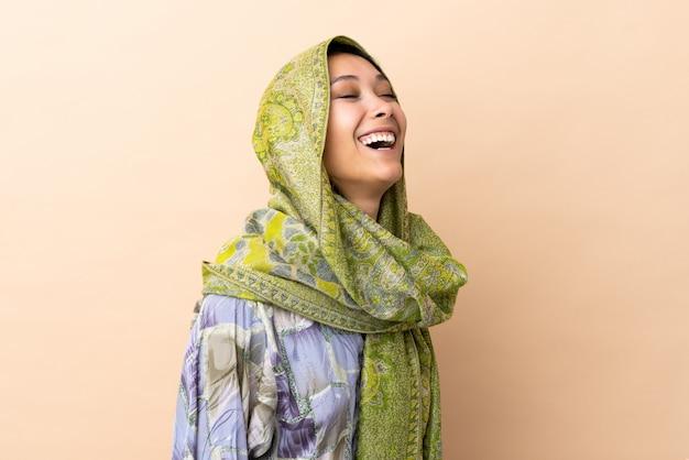 ベージュの笑いに分離されたインドの女性