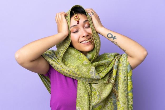 笑って紫色の背景に分離されたインドの女性