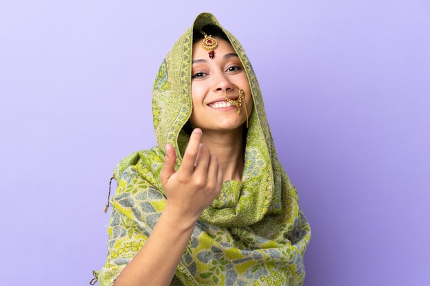 Indian woman isolated on purple space inviting to come with hand. happy that you came