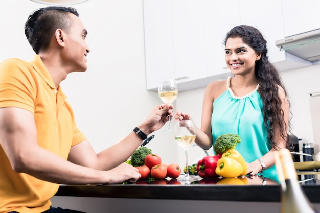 Indian woman and man in kitchen with red wine