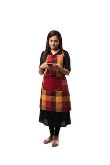 흰색 배경 위에 절연 서있는 동안 스마트 폰을 사용하는 앞치마에 인도 여자 또는 여성 요리사
