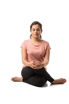 インドの女性または女の子が白い背景の上に孤立して座ってヨガのアーサナまたは瞑想またはディヤーナを実行します。